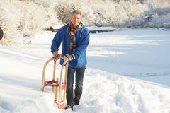 Middle Aged Man Standing In Snowy Landscape. Holding Sledge Stock Image