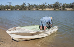 Middle-aged Man Starting Motor in Fishing Boat. Stock Image
