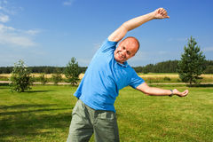 Middle-aged man streching. On grass Stock Image