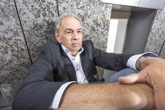 Middle-aged man is sitting desperately on the floor Stock Images