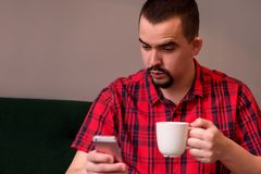 Middle-aged man with surprised face sitting on green sofa with mug of coffee and reading or watching something on smartphone stock images