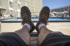 Middle aged man on swimning pool sunlounger wearing trekking shoes. Inappropriate shoes for summer royalty free stock image