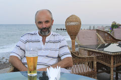 Middle-aged man at a table. In a cafe by the sea Royalty Free Stock Photography