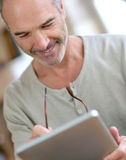 Middle aged man taking eyeglasses to read an ebook Royalty Free Stock Image