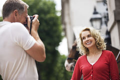 A middle-aged man taking a photograph of his partner in front of Horse Guards Royalty Free Stock Photography