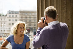 A middle-aged man taking a photograph of his partner by Trafalgar Square Royalty Free Stock Photography