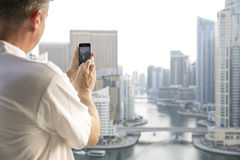 Middle aged man taking a picture of a marina view from his balco Royalty Free Stock Photography