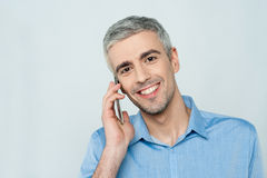 Middle aged man talking on cell phone. Happy mature man talking on mobile phone Royalty Free Stock Photos