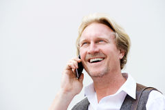 Middle aged man talking on mobile phone against white wall Royalty Free Stock Photo