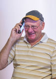 Middle-aged Man Talking on Mobile Phone. A middle-aged man smiles as he enjoys a conversation on his mobile phone Royalty Free Stock Image