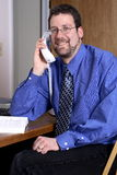 Middle-aged man talking on the phone. Middle-aged man using the telephone in a home office Stock Photo