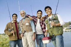 Middle-aged man with three sons on fishing trip. Middle-aged man with three sons holding fishing rods, smiling, (portrait stock photo
