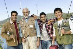 Middle-aged man with three sons on fishing trip. Middle-aged man with three sons holding fishing rods, smiling, (portrait royalty free stock photo