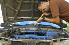 Middle-aged man trying to repair their own cars. Royalty Free Stock Photos