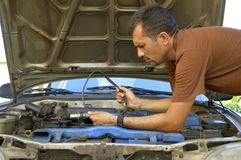 Middle-aged man trying to repair their own cars. Stock Photography