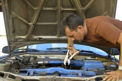 Middle-aged man trying to repair their own cars. Royalty Free Stock Images