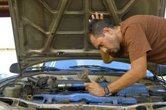 Middle-aged man trying to repair their own cars. Stock Photos