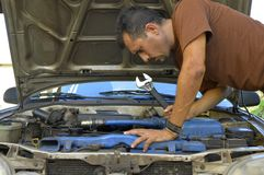 Middle-aged man trying to repair their own cars. Royalty Free Stock Photo