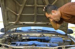 Middle-aged man trying to repair their own cars. Royalty Free Stock Image