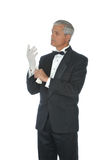Middle Aged Man in Tux Putting on White Gloves Royalty Free Stock Images