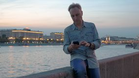 Middle aged man uses mobile phone on embankment in dusk. Middle aged man in denim shirt uses mobile phone on city embankment against calm river and lit buildings stock video