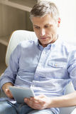 Middle-aged man using digital tablet at home Stock Image