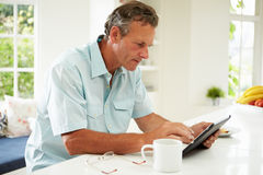 Middle Aged Man Using Digital Tablet Over Breakfast. Sitting At Kitchen Counter With Hot Drink royalty free stock image