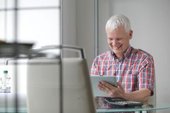 Middle-aged man using a high tech tablet PC Stock Images