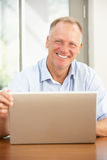 Middle Aged Man Using Laptop At Home Stock Images