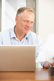 Middle Aged Man Using Laptop At Home Royalty Free Stock Images