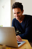 Middle aged man using laptop at home Royalty Free Stock Photography