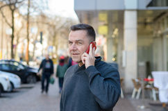 Middle aged man using mobile in city. Half body portrait of middle aged man using mobile in city street Stock Photos