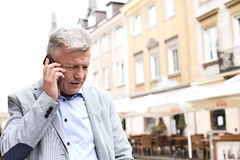 Middle-aged man using mobile phone in city Royalty Free Stock Images