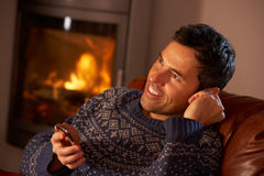 Middle Aged Man Using MP3 Player By Cosy Log Fire. Sitting on comfortable sofa Royalty Free Stock Photos