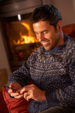 Middle Aged Man Using MP3 Player By Cosy Log Fire Stock Image