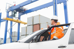 Middle-aged man using walkie-talkie while standing at car door in shipping yard Royalty Free Stock Photography