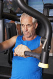 Middle Aged Man Using Weights Machine In Gym Stock Image