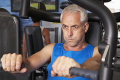 Middle Aged Man Using Weights Machine In Gym Stock Images