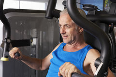 Middle Aged Man Using Weights Machine In Gym Royalty Free Stock Photo