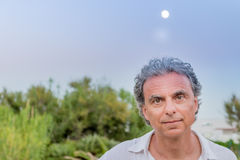 Middle-aged man visiting seaside town. Middle-aged man in white shirt while visiting seaside town, Vieste in Italy, known as the Pearl of Gargano stock photography