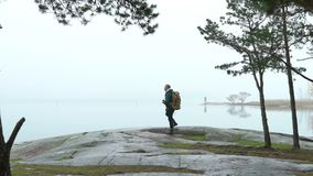 A middle-aged man watching wildlife through binoculars on a rocky shore of the sea on a misty autumn morning. stock footage