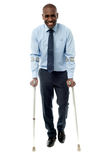 Middle aged man walking with two crutches stock image