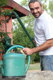 Middle-aged man with watering can Stock Images