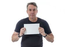 Middle-aged man wears black t-shirt. He holds a white paper. Stock Photo