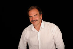 Middle aged man in white shirt. A studio portrait of a middle aged man in an open collar white shirt.  Black background.  Man looks somewhat like Burt Reynolds Royalty Free Stock Image