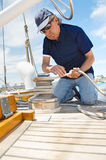 Middle-aged man winching rope on yacht Royalty Free Stock Photo