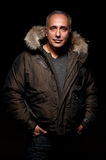 Middle aged man in winter coat. Portrait of middle aged man in winter coat over dark background Royalty Free Stock Photo