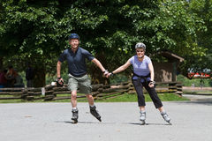 A middle aged man and woman hold hands while rollerblading in a park Stock Image