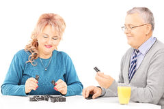 Middle aged man and woman sitting at table and playing dominos Stock Images