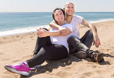 Middle-aged man and woman in white T-shirt sitting on the beach. Pair of middle-aged men and women in white T-shirt sitting on the beach Stock Image
